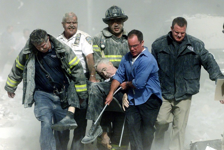 New York firefighters and rescue workers carry fatally injured fire chaplain Franciscan Father Mychal Judge from the wreckage of the World Trade Center in New York in this Sept. 11, 2001. Father Judge was administering last rites to victims of the terrorist attack when he was caught in the building's collapse. (CNS photo/Shannon Stapleton, Reuters)
