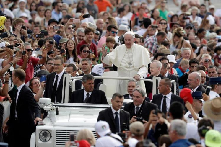 Pope Francis waves to faithful as he is driven through the crowd ahead of his weekly general audience, in St. Peter's Square, at the Vatican, on Wednesday, August 31. (Photo copyright Andrew Medichini/AP)